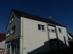 Wohn- und Geschäftshaus ohne Dachüberstände vor der energetischen Sanierung zum KfW-Effizienzhaus.